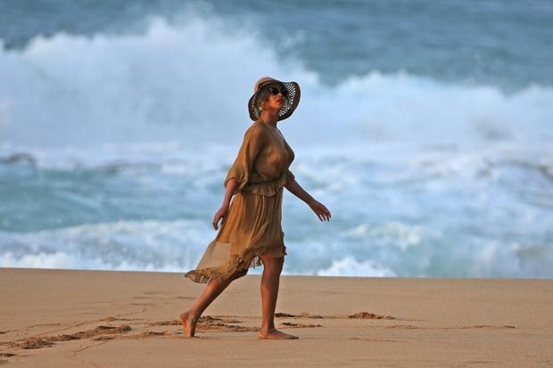 Beyonce se je ob sončnem zahodu psrehodila po plaži v čudoviti, lahkotni obleki v kaki barvi in z modnim klobukom. …